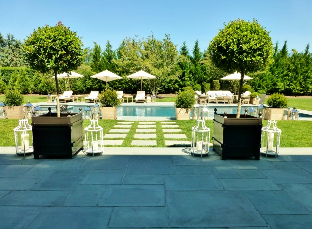 The terrace leads down to the amazing pool area with umbrellas and chaise lounges.