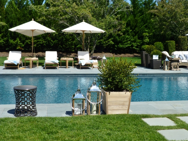 A detail of the lovely chaise lounges beneath useful umbrellas found poolside at the 2014 Hampton Designer Showhouse.