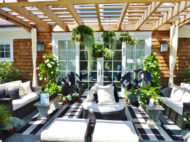 The terrace outside the quaint little pool house featured black and white striped outdoor carpets and accents under a lovely pergola.