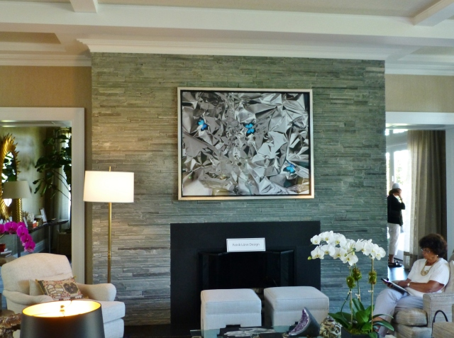 Across the room is the fireplace with a grey stacked stone tile.
