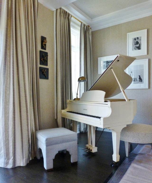 In the opposite corner of the great room, resides a stunning white baby grand piano (worthy of Liberace, himself!).  The piano stool is an identical match those placed in front of the fireplace.  Another oval ottoman is tucked under the body of the piano and white-framed black & white photographs are hung asymmetrically above.