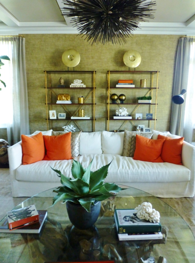 The living room has entrances from either side of the great room fireplace.  This image is your first impression upon entering the room.   The pair of gold metallic etageres are beautifully arranged and the large comfortable sofa has bold pillows that inject the bold orange accent color into the room's design.