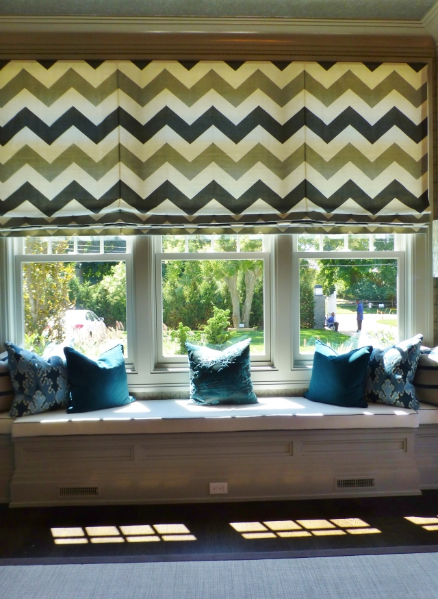 To the left of the main seating area was this ample window seat overlooking the front lawn.  The designer chose a graphic chevron pattern for the single large roman shade.  Custom pillows in contrasting colors look so inviting here!