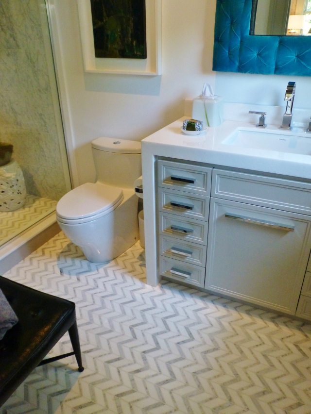 Just off the library is this beautiful full bath.  The chevron tile floors echo the window treatment fabrics in the adjacent room.  Notice the white waterfall countertop on the vanity and how it wraps around and down the side.
