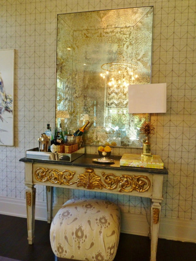 Here's a detail of the large antiqued mirror above the console.  It actually has reverse gilded (eglomise) patterns on it--absolutely gorgeous!   The brass pinecone lamp is interesting--it looks vintage to me.   I also thought this was a terrific location for the designer to place a tray of beverages, creating a make-shift bar area.  Something every library should have, don't you think?