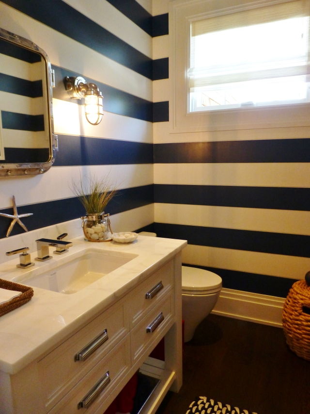 The adjoining powder room is also clad in ship-lap siding, painted in alternating stripes.  This contributes to the updated nautical theme, along with the ship lights and riveted metal framed mirror.  The rope basket in the corner gives some texture and warmth too.  This is a terrific powder room!