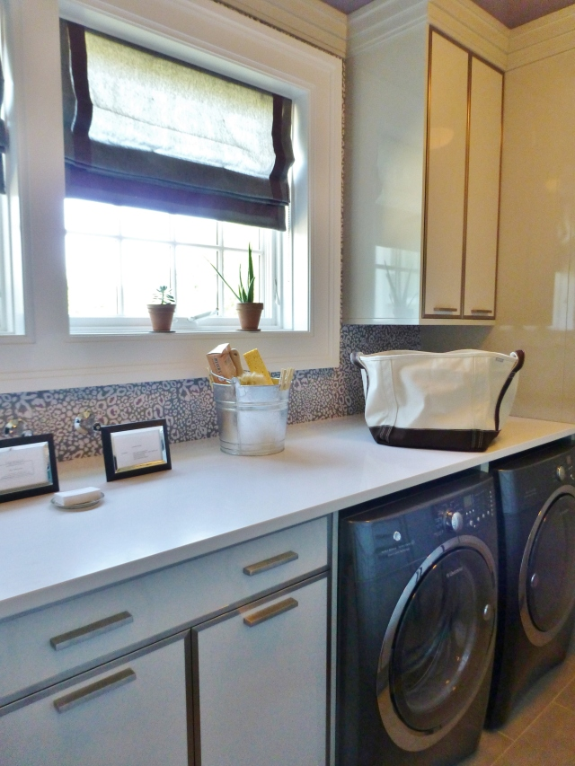 The laundry room at the 2014 Hampton Designer Showhouse was long and narrow.  I love that the designers kept things clean and simple, with tailored roman shades at the windows, white countertops and white cabinetry with sleek nickel trim.