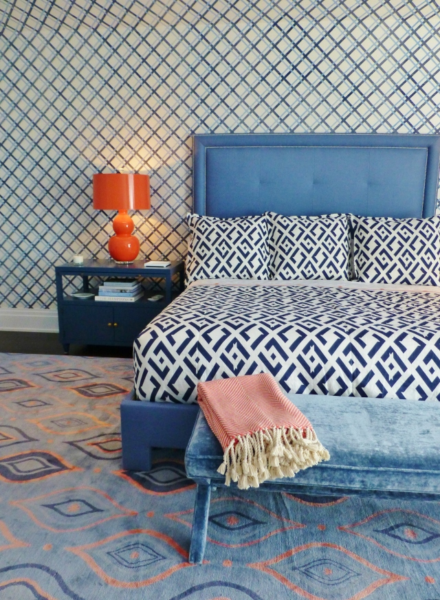 The bed features a solid blue upholstered headboard with double nailhead trim.  The bed, painted nightstands, and bold orange lamps provide a place for your eye to rest.