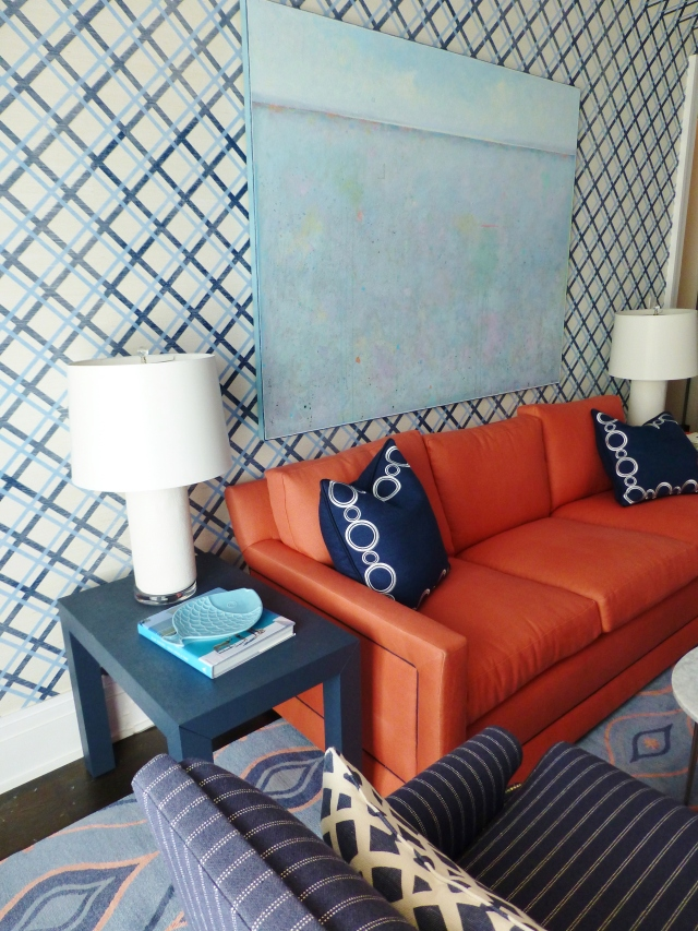Across the room in a sitting area, featuring a bold orange sofa, echoing the color of the bedside lamps.  I really like the pinstripe chairs in a menswear-type fabric.