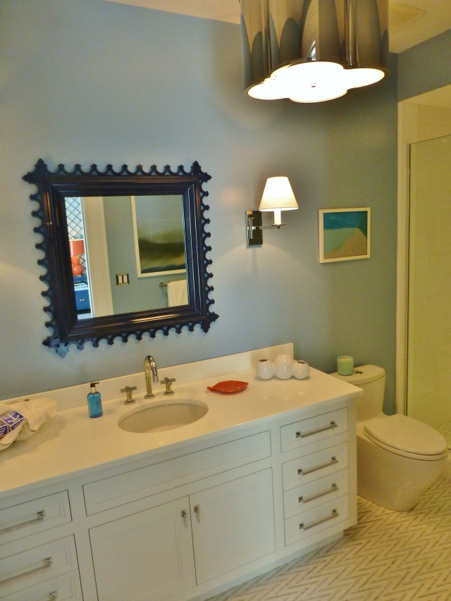 This bedroom has its own private bath, painted in a soft blue.  The designers chose a cute navy blue lacquered mirror and a terrific shiny nickel quatrefoil light fixture.