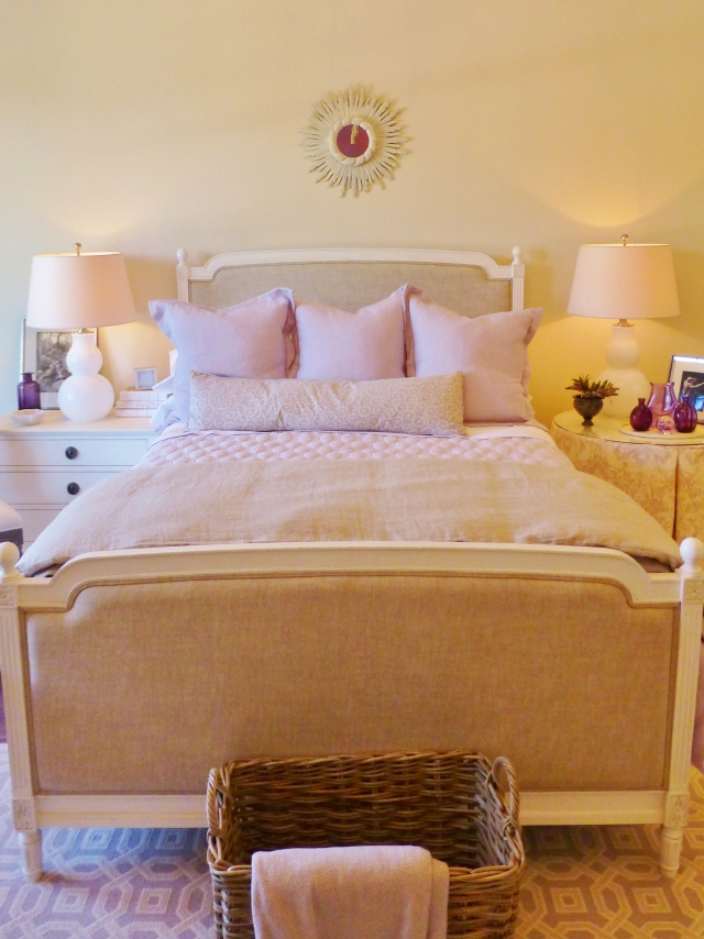 The French linen-upholstered bed is topped by lovely lavendar bedding.  The pair of white glass gourd lamps are quite pretty, as is the ivory starburst mirror above the bed.