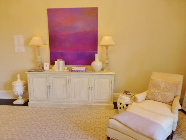Directly across from the bed is this painted dresser with bold modern art hung above. A comfy chair and ottoman reside in the corner.