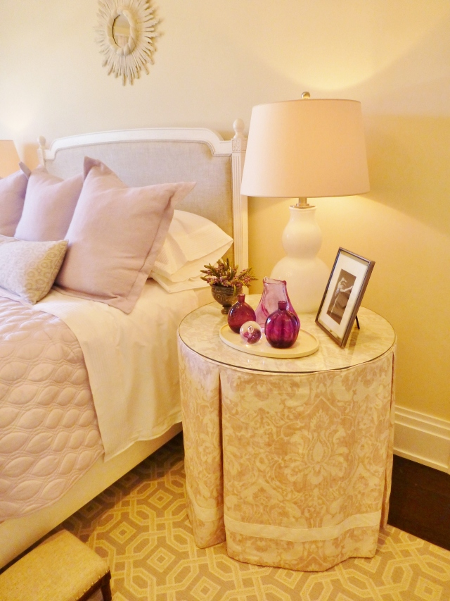 The designer chose to use mismatched end tables on either side of the bed.  At the right is this lovely skirted table.  The fabric is so pretty with its lavender damask pattern and I really like the added detail of the ivory ribbon tape, applied just a few inches from the hem. You can also take a closer look at the bedding in this photo.  Such a pretty combination of fabrics and textures were used.