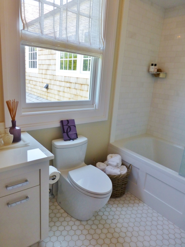 Here's just a quick peek into the en-suite bathroom.  Notice the honeycomb tile on the floor, which is especially nice.  The sheer roman shade is also pretty, but doesn't seem like it would provide much privacy.  Purple accessories are used sparingly to continue the bedroom's color scheme.