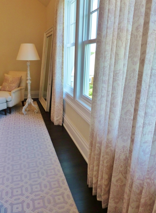 Here's a shot featuring the pretty linen draperies.  They're very simple full-length panels in the same printed damask pattern as the skirted table by the bed.  They're very elegant and subtle and the scale of the pattern combines beautifully with the area rug.