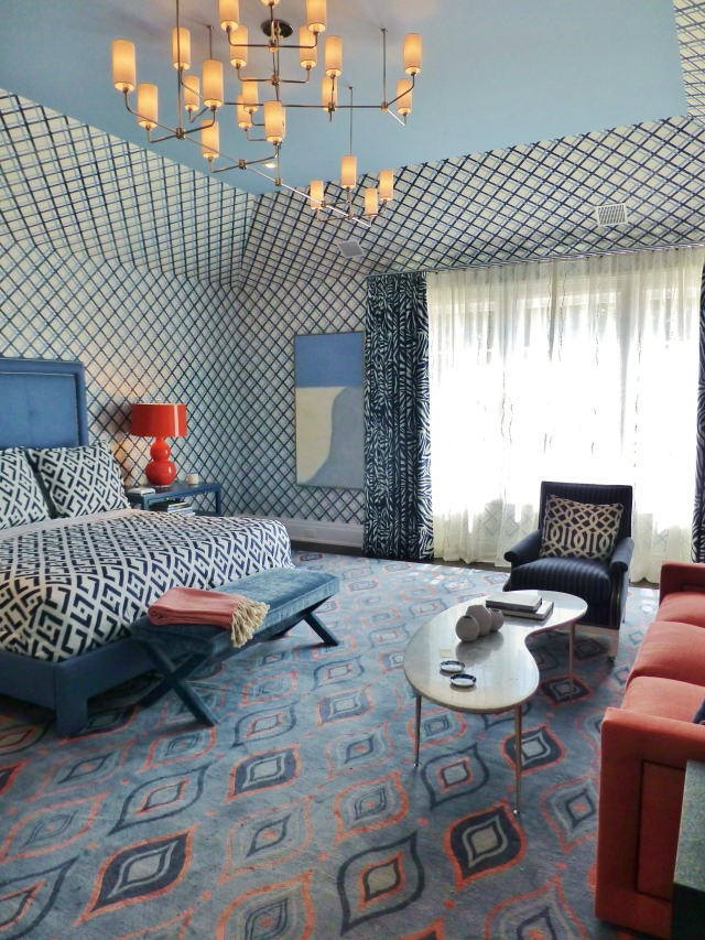 The blue and orange guest bedroom designed by Mabley  Handler Interior Design.  Notice the bold trellis pattern wallpaper wraps up and onto the side of the tray ceiling.  There is a lot of pattern here, but the scale and intensity of each pattern holds its own.