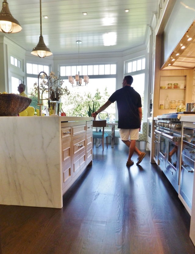 Entering the kitchen from the dining room, you can appreciate the rich wood floors, a wonderful contrast to the white beadboard ceiling. You'll also notice the waterfall marble top on the large kitchen island.