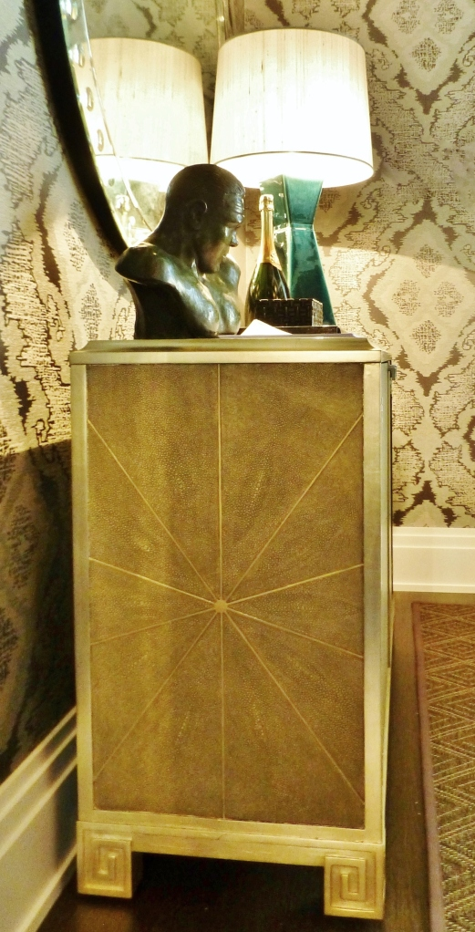 This shagreen cabinet is one of a pair that flanks the glassed in wine enclosure.  Shagreen is a luxurious material commonly made from the skins of sharks and rays.  It's often used to cover books and boxes...even the hilts of swords.  Shagreen is not often used to cover an entire piece of furniture because it is a very expensive substance.  The design of these chests is especially pretty, with the starburst pattern on the side and the silver-leafed details, including the Greek Key feet.