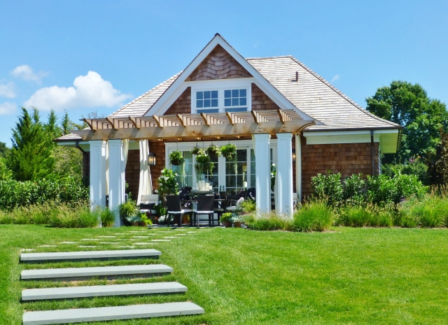 The opposite side of the pool house/guest cottage features a nearly identical terrace.  This one features a dining table and chairs, but has the same elegant black and white color scheme and elaborate hanging baskets.  Notice the chunky square white columns at the corners of the pergola.  The designer also placed white outdoor grommet draperies inside the pergola, to soften the look.
