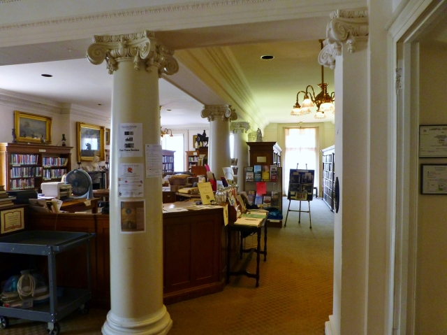 The main entry brings you up some stairs and into the library which was created in 1910. As an independent circulating library, it lends current fiction, popular bestsellers, nonfiction, children's literature, classic literature and reference materials.  Walls between bedrooms were removed and beautiful columns with dentil moldings were added to open up the second floor of the mansion.