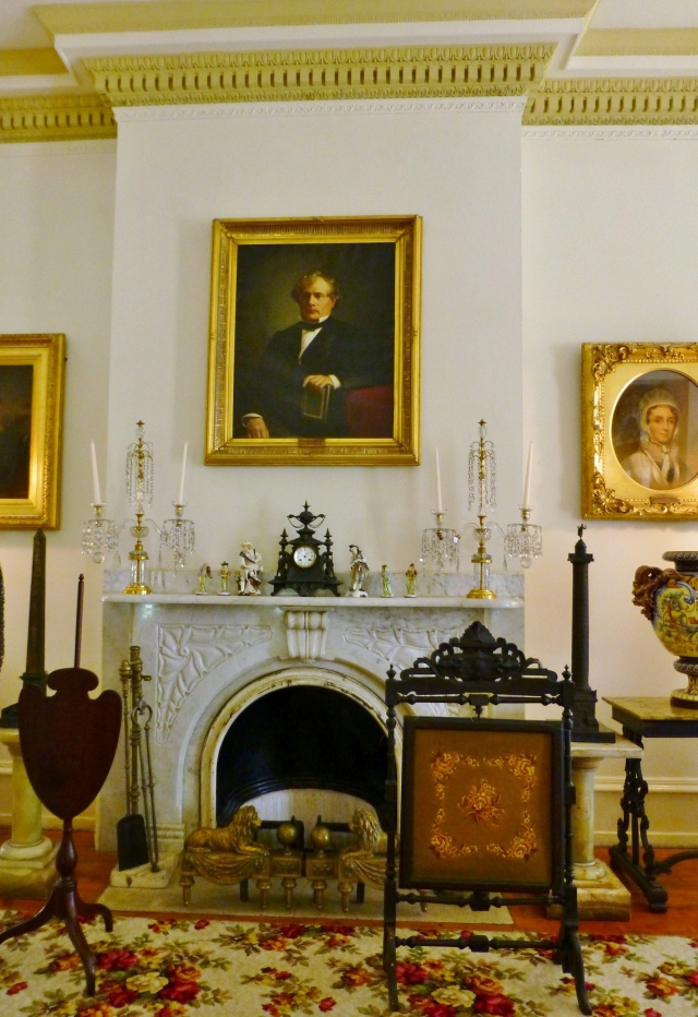 Portraits of family members are hung on the walls and various furnishings are scattered about.