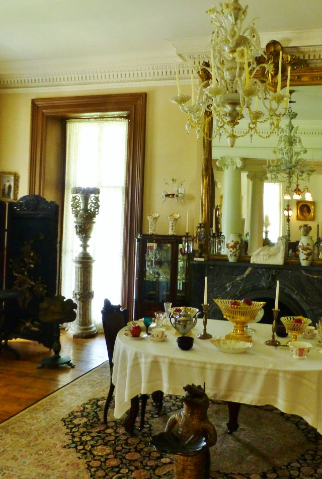 The former dining room with it's table and various pieces of tableware.