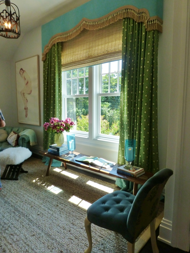 Here's an image of the fabulous window treatments.  The designer chose to use woven wood shades under bold green dotted drapery panels.  A turquoise cornice board with fabulous tassel fringe adds an exotic feel.  I really like the bold color combined with natural elements that give an almost tropical feel.  That long rustic wooden bench is really cool too, don't you think.  It's wonderful how the light is just falling down on it in the image!