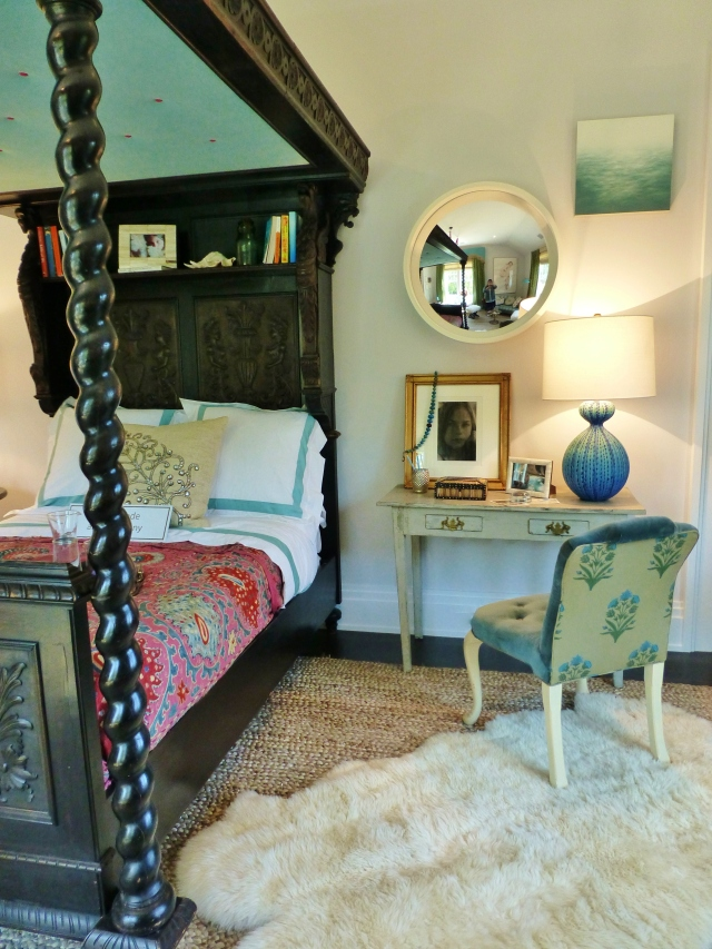 To the right of that fabulous Jacobean bed (which acts almost like sculpture in the room) the designer placed a small desk, which also serves as the night stand.  That textural blue and turquoise gourd lamp is amazing!! And the upholstered chair with the rolled back is stunning too!