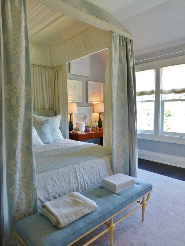 A serene bedroom by the famous Phoebe Howard, features soft whites, ivories, and the palest of blues.