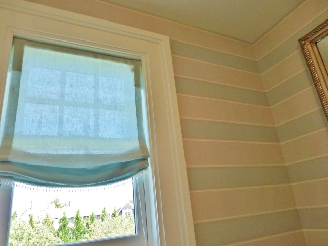 Here's a quick peek inside the en-suite bathroom.  Here a relaxed roman shade was used with a little glass bead trim.  This looks very feminine and pretty with the soft tan and blue horizontal-striped wallpaper.