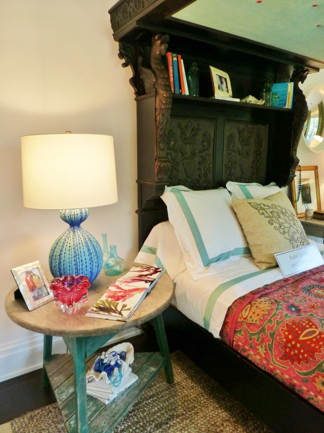 At the left side of the bed, a primitive round table was used with a matching gourd lamp.  The bedspread is so colorful and fun in contrast to this serious dark bed.  The carving on the bed is magnificent!  Did you notice that great little shelf inside the top of the headboard?  What a terrific place to store books and cherished items.  This antique bed is like a room within the room!