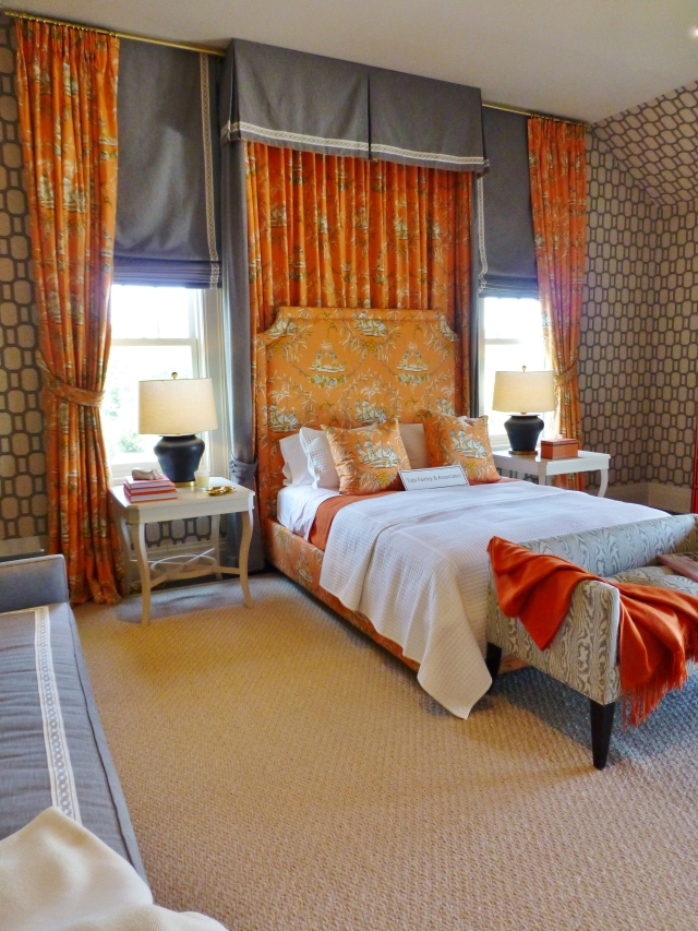 Here's a closer look at the bed wall, with it's full length draperies in the orange toile (hung all the way to the ceiling).  Tobi used grey roman shades underneath the draperies and used a beautiful tape to band the edges of both the shades and the bed hangings. The painted white side tables with their curvy legs are just perfect with the shape of those chunky charcoal lamps! The almost wall-to-wall area rug, provides a solid background and much needed relief from the heavily patterned wallpaper.  This is the perfect rug for the space.