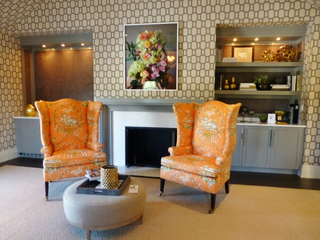 Directly across from the foot of the bed is a lovely seating area and fireplace.  There are even built in bookshelves at the right and a wet-bar at the left!   The curvy wing-back chairs are covered in the same orange toile, and a round grey ottoman is used as a cocktail (or coffee if you prefer) table. The colorful artwork above the mantel is truly amazing.  At first glance it just looks like a photograph of flowers, but upon closer inspection, once notices an eye peeking out from the foliage and then naked shoulders with fingers clutching the bouquet the bottom of the image.  I love art that takes a few minutes to reveal itself!