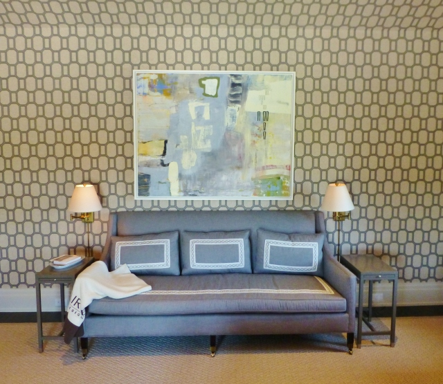To the left of the bed (on the same wall as the entry door) is a gorgeous sofa upholstered in the same grey as the shades and bedhangings and using the same beautiful tape on the seat and pillows. A large piece of abstract artwork hangs above the sofa, flanked by swing arm lamps for reading. The side tables are very small and tailored, echoing the lines of the streamlined sofa.