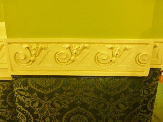 The color scheme chosen by Yarosh is very bold with a strong celery green above the detailed chair rail with Grecian motifs.   Below the elegant wave border the walls are upholstered in an absolutely gorgeous damask jacquard fabric featuring peacock blue and green.
