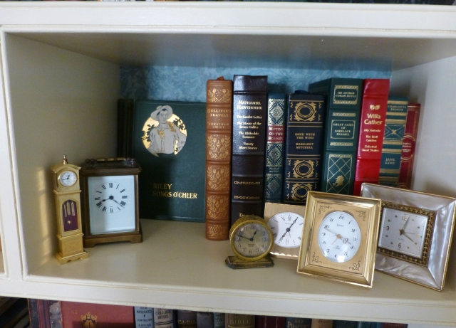 Many of our clocks are displayed in our living room bookshelves, alongside antique and vintage books I've been collecting since High School.  Here you see a grouping of small tabletop clocks, amongst some leather bound books.