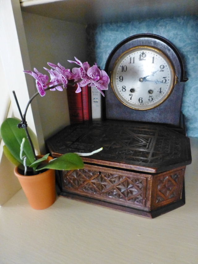This clock is tucked back in a corner, behind a lovely antique chip carved box.