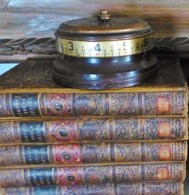 An unusual desk clock sits atop a stack of leather-bound books on our fireplace mantel.