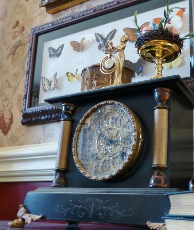This turn-of-the-century slate 'black clock' is in our dining room, where an antique pocket watch is displayed on top. The framed butterflies were a gift from a dear friend and were collected from all over the world.