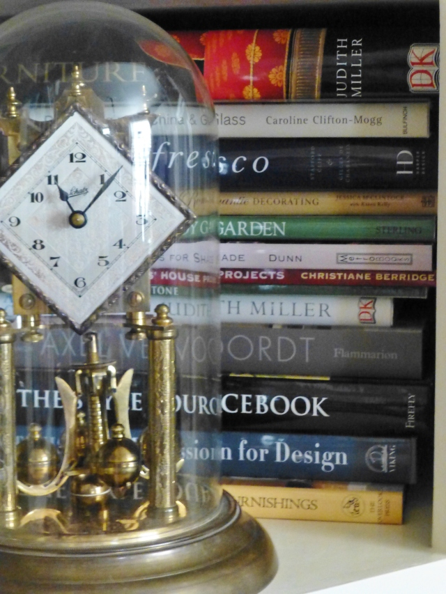 This glass-domed anniversary clock resides in front of my vast collection of interior design books.