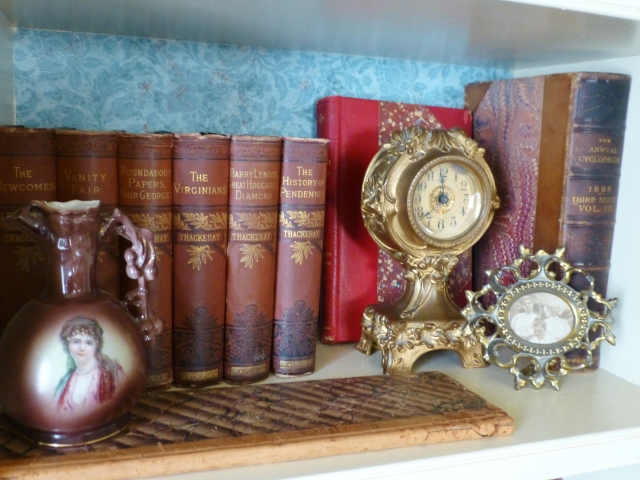 A bronze, gilded clock by Jennings Brothers enjoys a spot with some favorite antique books and accessories.