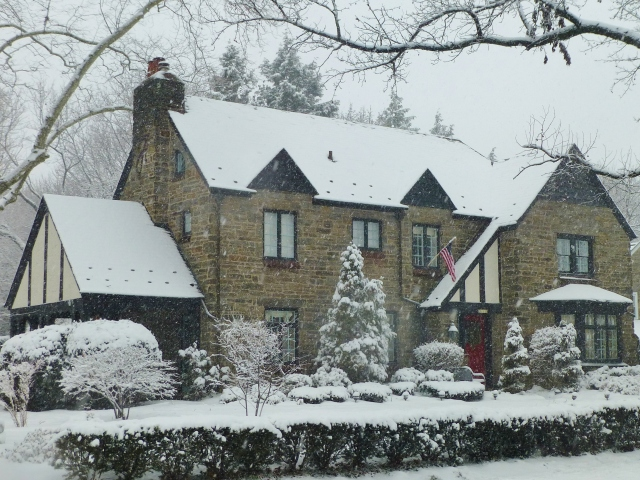 This large stone home has many Tudor details, painted dark, almost black.  I really like the high contrast here...especially with their red door and all that white snow.