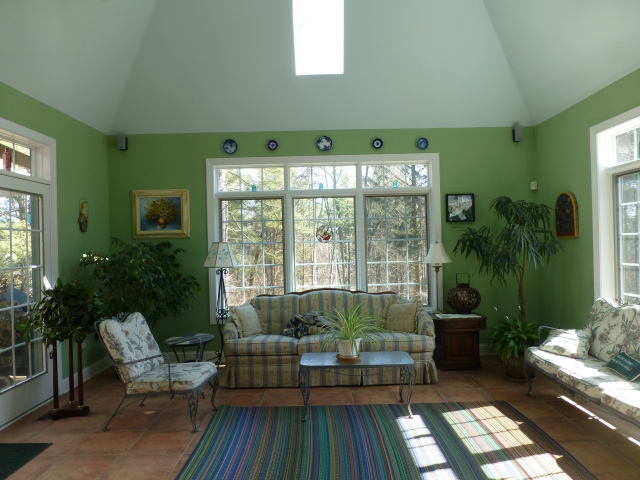 BEFORE:  Bold green on the walls and a soft turquoise on the tray ceiling are vibrant and exciting in this conservatory, but the vintage iron furniture is leggy and small, while the striped rug is undersized and not relevant to the furniture placement.