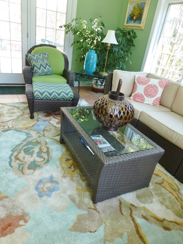 A comfortable chair and ottoman provide another spot to relax and take in the outdoor views, in the vibrant space.