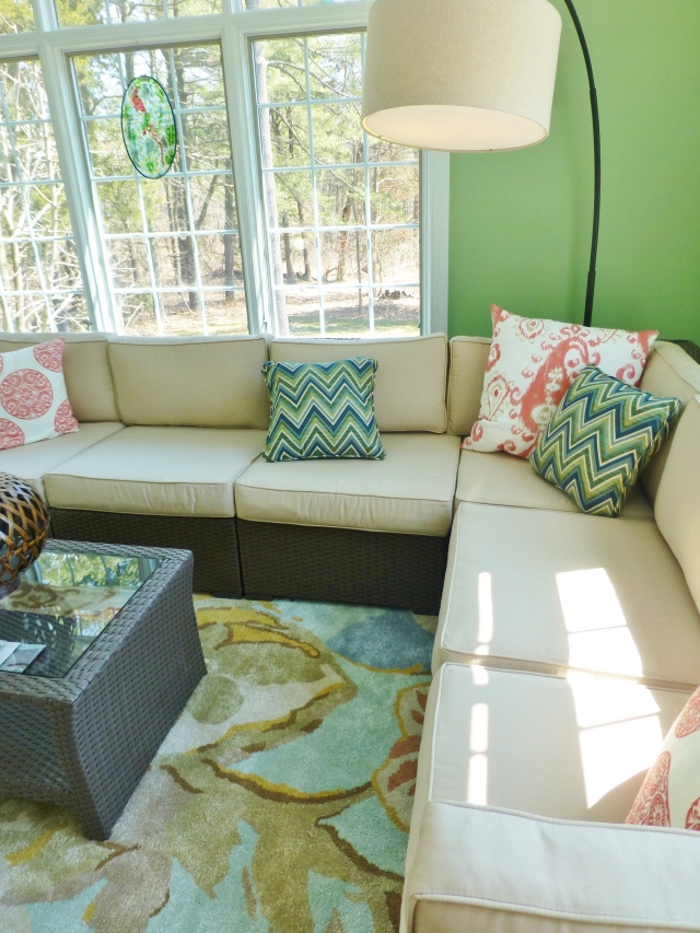 A tall arc lamp provides nighttime reading light and anchors the corner of the sectional.   Colorful pillows scattered throughout, add pattern and provide pops of color on the neutral sectional cushions.