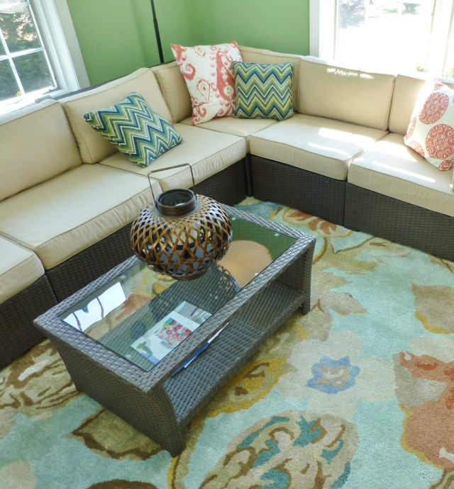 The artful wool rug provides soft comfort underfoot, while acting like artwork in the large space.  The colors tie the whole room together and softer color palette helps tame the vibrant green walls.