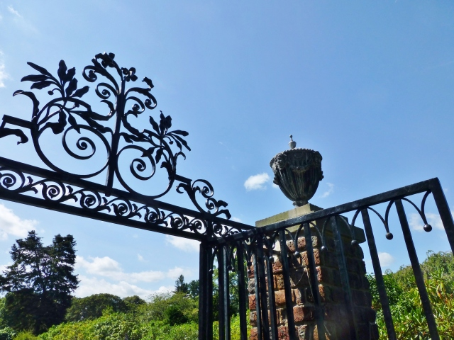 Here's a detail of the ornate gates at the pool entrance.   I adore the leaf and floral design of the pediment.  And those urns...absolutely gorgeous with their floral swags and Grecian faces!