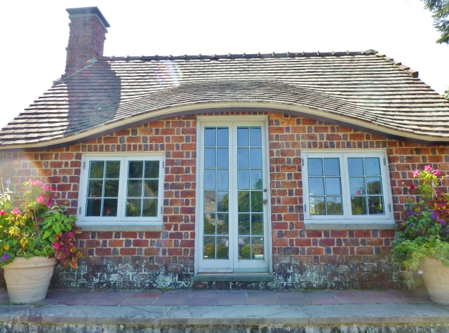 A closeup of the charming English cottage with it's eyebrow roofline.  Notice the detail of the brickwork patterns...who wouldn't love to have such a charming poolhouse?