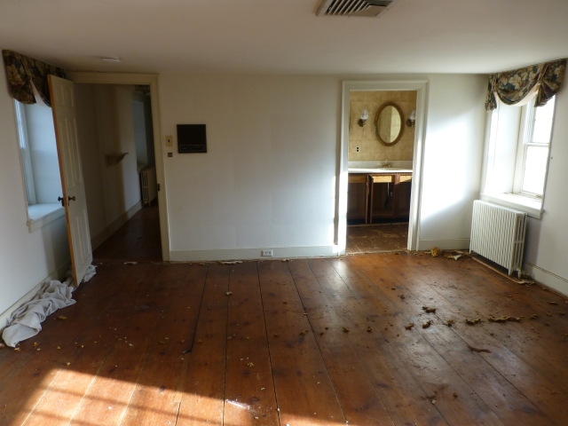 As you continue rotating to the left, the bathroom door (at the right) and entry door from the hallway (on the left) come into view. The large brown thing on the wall is an old intercom system that runs throughout the house.